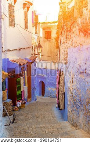 Gift Shop On Empty Narrow Lane In Medina Of Chefchaouen, Morocco. Moroccan Traditional Clothes Hang