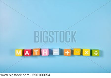 Flat Lay, Top View Of Bright Colored Math Symbols On Wooden Blocks On Blue Color Background With Cop