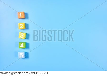 Flat Lay, Top View Of Bright Colored Numeral Cubes With Numbers 1 To 5 Wooden Bricks On Blue Color B