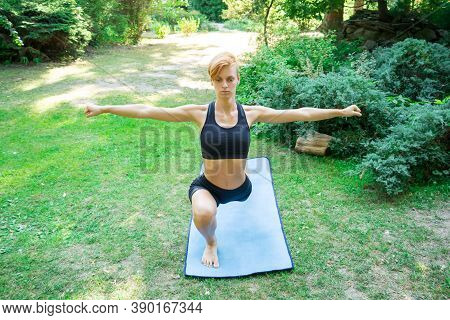 Woman Doing Yoga In The Park, Young Girl Doing Various Wellness Exercises, The Concept Of A Healthy