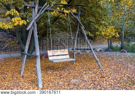 Empty Swing In An Autumn Park, A Wooden Swing Hanging On A Chain And Made By Hand, Against A Backgro