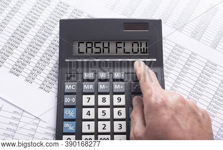 Cash Flow Word On Calculator On Financial Documents With Male Hand, Top View, Flatly