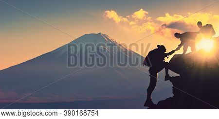 Young Asian Couple Hikers Climbing Up On The Peak Of Mountain Near Mountain Fuji. People Helping Eac