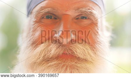 Portrait of smiling handsome cool senior man with beautiful big white beard and mustache. Closeup, shallow DOF.
