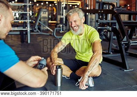 Exercising With Personal Trainer. Happy Middle Aged Man Discussing Something With Fitness Instructor