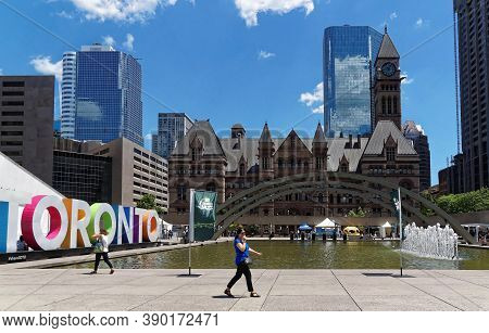 Toronto, Canada - 06 27 2016: A Woman Walking In Front Of A Fountain At Nathan Phillips Square. The