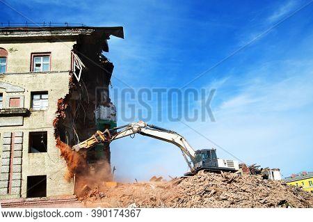 Excavator Demolishing A Brick Building. Machinery Demolishing Building