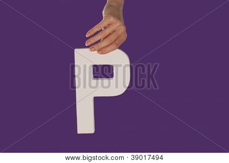 Female hand holding up the uppercase capital letter P isolated against a purple background conceptual of the alphabet, writing, literature and typeface