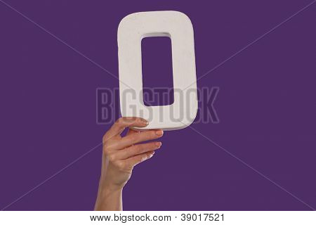 Female hand holding up the uppercase capital letter O  isolated against a purple background conceptual of the alphabet, writing, literature and typeface