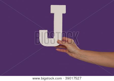 Female hand holding up the uppercase capital letter J isolated against a purple background conceptual of the alphabet, writing, literature and typeface