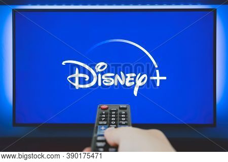 Wroclaw, Poland - Oct 13, 2020: Man Holds A Remote Control. Disney+ Logo On Tv Screen In Background.
