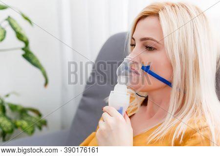 Woman Makes Inhalation Nebulizer At Home. Holding A Mask Nebulizer Inhaling Fumes Spray The Medicati
