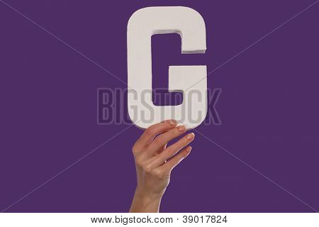 Female hand holding up the uppercase capital letter G isolated against a purple background conceptual of the alphabet, writing, literature and typeface
