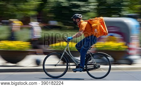 Bucharest, Romania - August 04, 2020: A Takeaway Food Delivery Courier On A Bike In High Speed In He