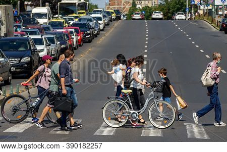 Bucharest, Romania - July 23, 2020: People Cross The Street In Downtown Bucharest, Romania.