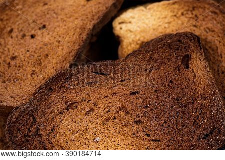 The Texture Of Toasted Pieces Of Bread. Croutons On A White Background. Dark Dry Bread.