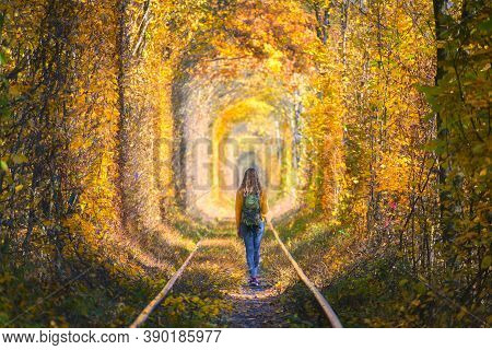 Young Woman Walking On The Railroad In Tunnel Of Love In Ukraine In Autumn At Sunset. Girl With Back