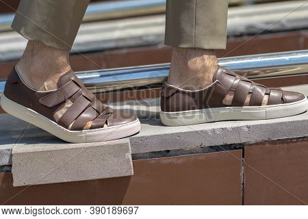 Men's Sandals On The Leg Are Close-up Brown With Shortened Trousers