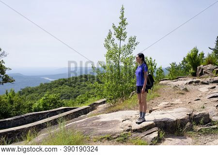 A Chinese Woman Standing On Top Of Prospect Mountain In Lake George Overlooking The Landscape.