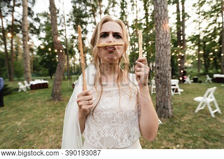 Happy Bride,funny Bride,crazy Bride,cheerful Bride Holds Edible Sticks In Her Hands And Lips,crazy B