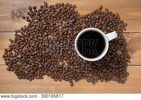 Balck Coffee In White Cup On A Wooden Table Surrounded By Coffee Beans.