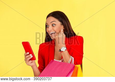 Excited Euphoric Mid Adult Woman Using Smartphone Holding Shopping Bags Pumping Fist In Happiness Is