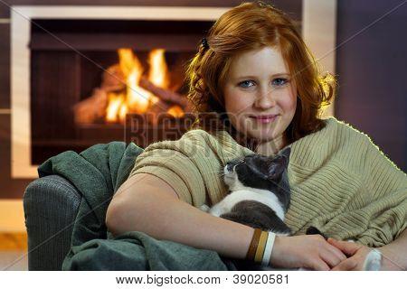 Teenage girl sitting at fireplace fondling cat.