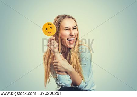 Young Woman Blonde Girl With Long Hair Playing With Yellow Emoji Candy On A Stick Standing Isolated