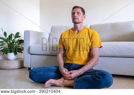 Handsome Man With Eyes Closed Sitting On Floor In Lotus Pose And Meditating At Home