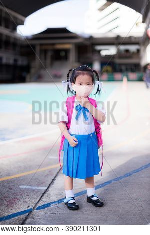Kindergarten Student Carry Their Bags To School. Child Wear Cloth Mask To Prevent The Spread Of The