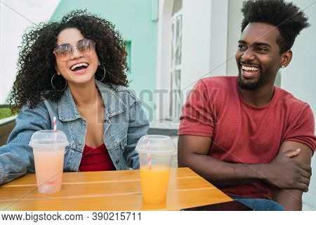 Portrait Of Two Afro Friends Having Fun Together And Enjoying Good Time While Drinking Fresh Fruit J