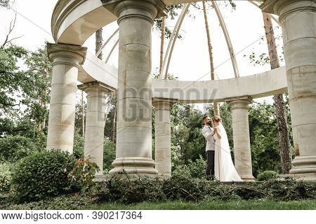 Bride And Groom On Their Wedding Day, Walking Outdoors In Spring Nature. Just Married, Happy Newlywe