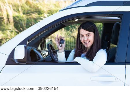 Pretty Woman Sitting In Car And Showing Keys