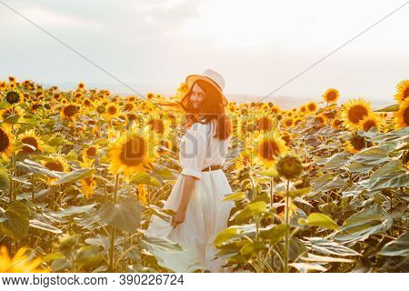 Young Beautiful Woman At Sunflowers Field On Sunset