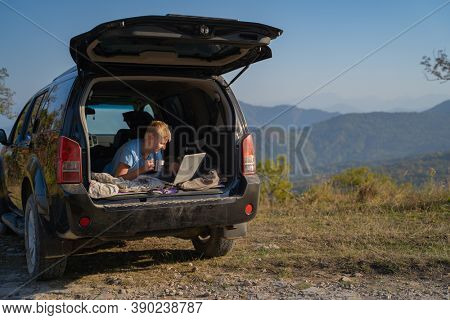 Young man resting in nature with an off-road vehicle resting in the trunk of a car. Uses a laptop for communication and Internet access