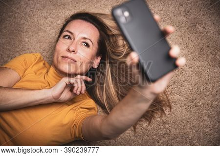 Happy mid-aged woman taking selfie with her smart phone at home