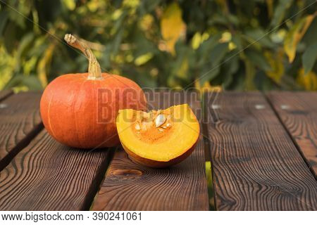 A Cut Piece Of Pumpkin And A Whole Pumpkin On The Table Against A Tree Background. Autumn Pumpkin Ha