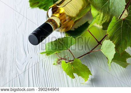 An Unopened Bottle Of White Wine And Grapevine On An Old Wooden Background. Wine On A White Table. C