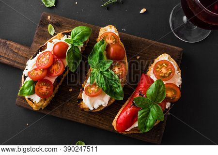 Bruschetta Sandwiches With Tomatoes, Cream Cheese, Grilled Paprika And Basil On Wooden Board, Close
