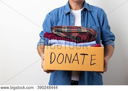 Man Holding Clothes With Donate Box On A White Background, Donation Concept.