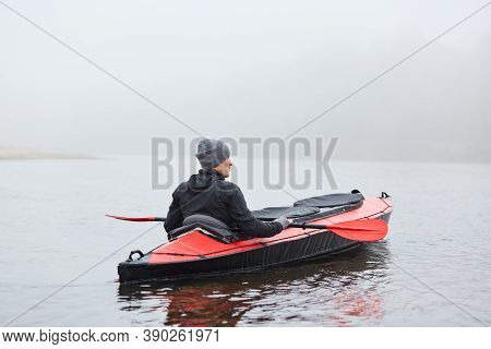 Young Handsome Man Paddling Canoe On Cloudy Day, Canoeing On Foggy Day, Back View Of Extreme Sportsm