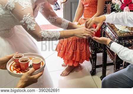 Closeup Of  Bride Serving Tea To Elderly During Wedding Ceremony. Chinese Word Celebration Is Inscri