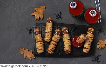 Spooky Sausage Mummies, Tomato Juice And Sauce For Halloween Party On Dark Wooden Board. Top View. F