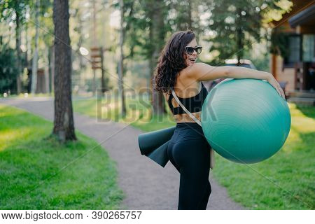 Outdoor Shot Of Happy Brunette Woman Carries Fitball And Fitness Mat, Wears Sunglasses And Sport Clo