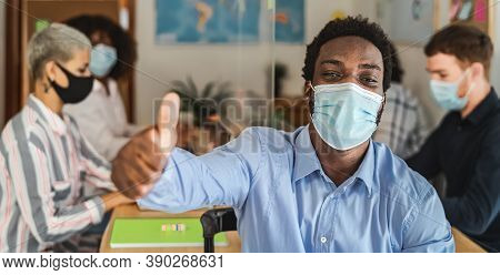 African Man Thumb Up Wearing Face Mask In Co-working Creative Space With Team Work - Young People Wo