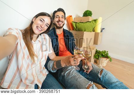 Happy Young Couple Taking Selfie While Celebrating With Champagne In New Home First Time - Change Ap
