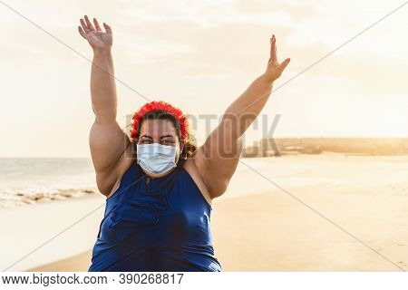 Happy Plus Size Woman Walking On The Beach While Wearing Face Mask - Curvy Overweight Model Having F