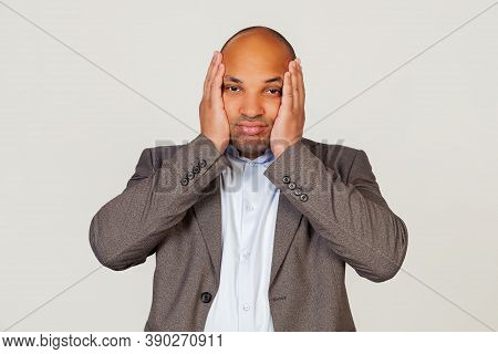 Young African American Guy Businessman Holding His Head In Hands With Unhappy Facial Expression Look