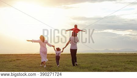 Asian Family Walking And Running On The Meadow At Sunset With Happy Emotion. Family, Holiday And Tra