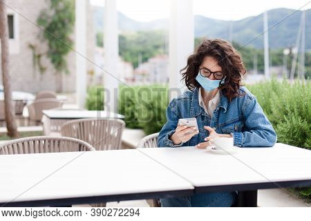 Woman Wearing Protective Mask In Empty Cafe Outdoors. Girl Using Mobile Phone. Social Distancing Dur